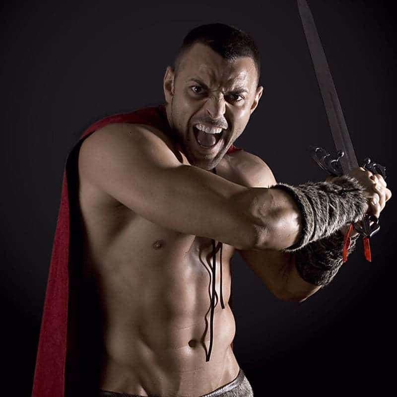 Joel Acosta stripper in Barcelona posing in a spartan suit with a sword